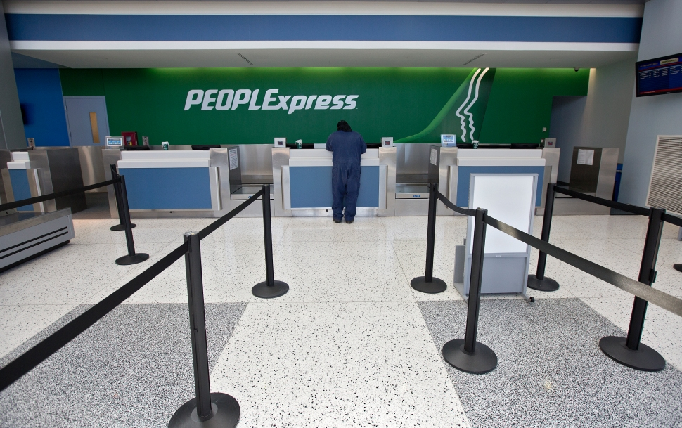 Dameon Walker waits at an empty People Express ticket counter to make adjustments to an upcoming flight from Newport News-Williamsburg International Airport on Friday. After one of the airline's planes was hit by a truck and its remaining plane experienced maintenance issues, People Express canceled all flights through October 15.