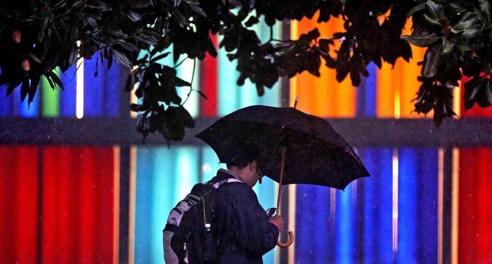 William and Mary student Luis Vargas walks beneath his umbrella while passing the windows of the Muscarelle Museum of Art as rain falls throughout the campus Wednesday evening.