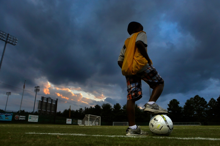 Atticus Kanara, 8, of Williamsburg waits on the sidelines to as a ball boy as ominous clouds swirl around a sun set before the start of William and Mary's soccer game against University of North Carolina's at Albert-Daly Field. (Photo by Jonathon Gruenke)