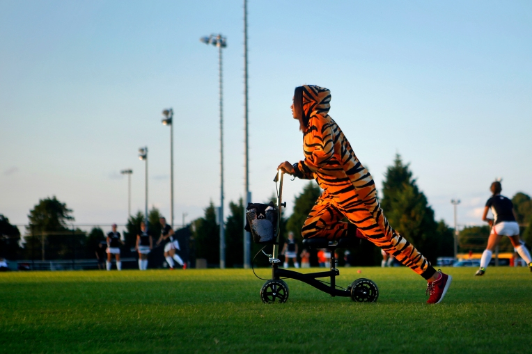 Kaila Atkins, 17, rides a scooter across the grass before the start of Wednesday's field hockey game between Tabb and Smithfield. Atkins, a senior on the team, broke her foot three weeks ago but didn't let the injury deter her from donning a tiger costume and cheering her team on from the sidelines. Tabb won the contest 6-0. (Photo by Jonathan Gruenke)