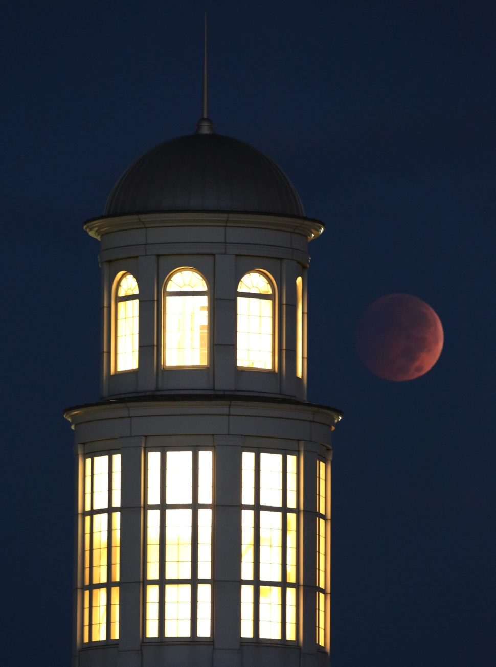 A full lunar eclipse glows in the early morning sky  Wednesday over the Trible Library at Christopher Newport University in Newport News, Va.  The eclipse was visible throughout North America, and here in the East between 5:15 a.m., reaching it's reach its peak at 6:25 a.m. (Photo by Adrin Snider)