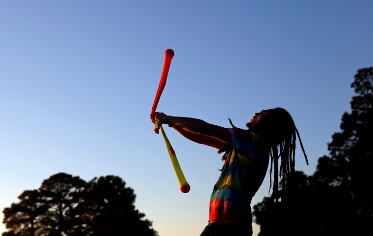 Tom Degnon of Carrollton practices poi dancing as the sun begins to set near Lion's Bridge Monday evening.