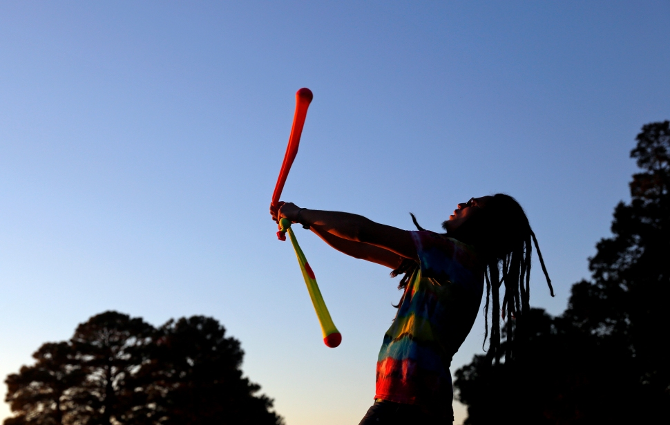 Tom Degnon of Carrollton practices poi dancing as the sun begins to set near Lion's Bridge Monday evening.