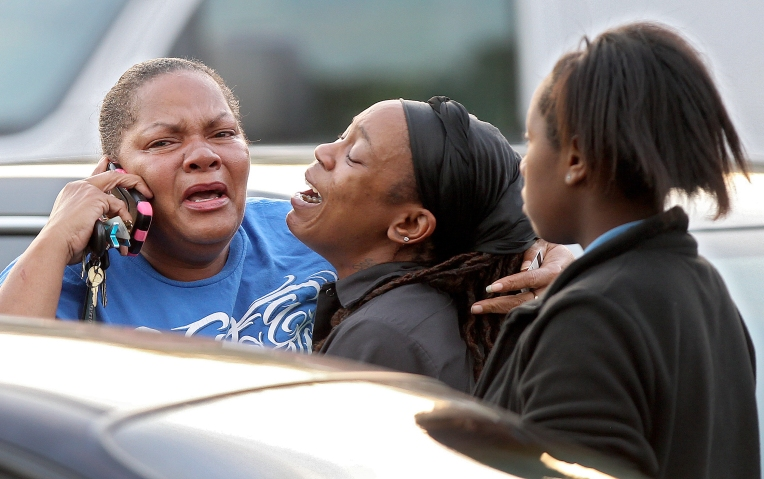 Friends and family of stabbing victim Taiwo Douglas-Wells react Wednesday evening in the parking lot of Newsome Park Elementary School. (Photo by Rob Ostermaier)
