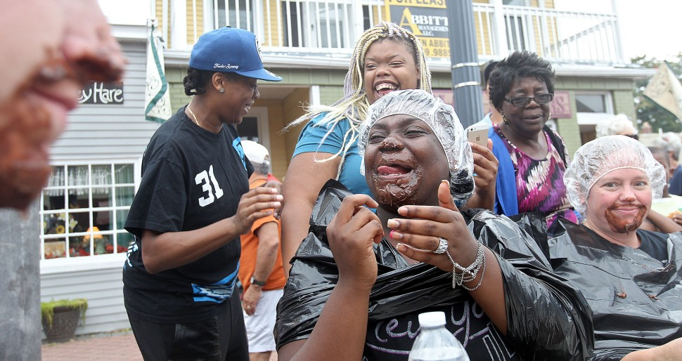 Zhane Gilder licks pudding from her face after competing in a pie eating contest at the Phoebus Fall Festival on Mellon St. Saturday. (Rob Ostermaier)
