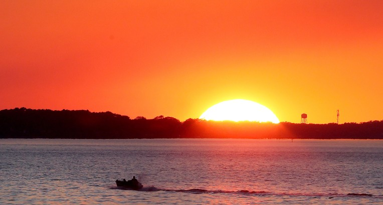 A small fishing boat heads out onto the James River Wednesday evening as the sun sinks below the horizon.