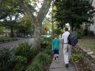 Jim carries a backpack as he walks with his son, Bradley, home from Hilton Elementary School on September 30. (Kaitlin McKeown)