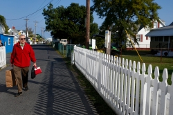 Dr. David Kemp walks down a street on Tangier Island Thursday morning to treat patients at the Riverside Tangier David B. Nichols Health Center. (Jonathon Gruenke)
