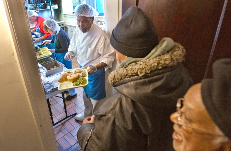 St. Vincent de Paul Catholic Church has a backdoor ministry that provides hot lunch-time meals weekly, Monday through Friday to those in need. Here, Head cook Leroy Bunch hands out a hot meal to those in need Wednesday. The church brought those in need of a meal inside to shelter them from them cold. (Joe Fudge)