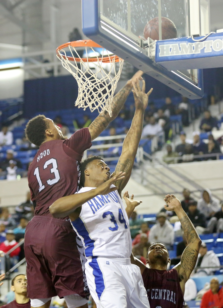 Hampton's Reginald Johnson puts up a shot between North Carolina Central's Enoch Hood and Dante Holmes during the first half of Monday's game at Hampton. (Kaitlin McKeown) For more.