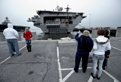 Family members stand near the USS Theodore Roosevelt waiting for its departure early Monday. The ship was delayed in its deployment until later due to a maintenance issue.
