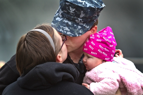 Brittney gets a last kiss from her man Petty Officer Third Class Dylan Bronaugh while little 5-month old Kayie 5 months looks on pier 4 at Norfolk Naval Station.