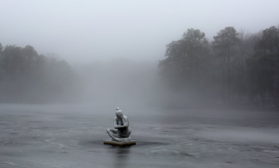 """Selene"" rests on Kettle Pond in Newport News surrounded by ice and fog early Wednesday morning. The 7-foot, 8,455-pound figure was sculpted by Italian artist Maria Gamundi. (Adrin Snider) For more photo."