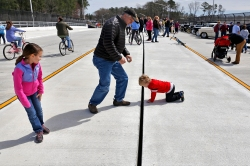 Nolan Murry, 4, inspects a gap in the median of City Center Boulevard as his sister, Carlin, left, and father, Greg Murray, center watch after Saturday's ribbon cutting ceremony and community celebration April 4, 2015. (Jonathon Gruenke)