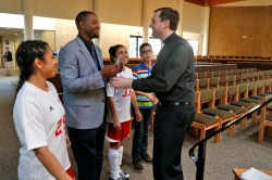 From left, Lexi Yau, Laderick Maynor, Alexandra Yau and Alex Yau practice handing oil to Father Sean Prince during a rehearsal for Holy Week at Immaculate Conception Catholic Church in Hampton. (Jonathon Gruenke)