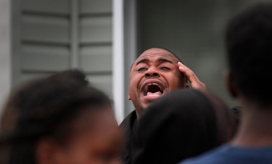 Minister Kenneth Ford sigs a hymn during a vigil for 13-year-old Jada Richardson and 17-year-old Domingo Santiago Davis Jr. who were killed last Monday night outside a party on 25th street in Newport News. (Rob Ostermaier)