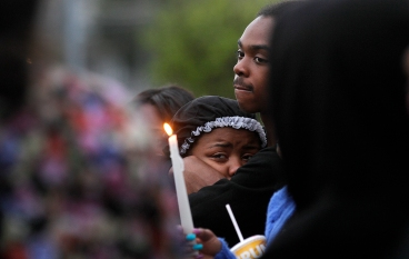 Friends and family of Jada Richardson and Domingo Santiago Davis Jr. comfort each other during a vigil outside home on 25th street where they were killed Monday night. (Rob Ostermaier)
