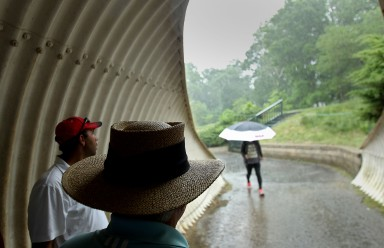 Volunteer Dave Bradley takes shelter in a tunnel running between the fourth and fifth holes at Kingsmill Sunday as thunderstorms delayed play.