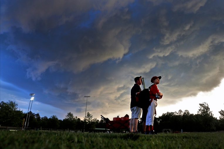 Todd Price, left, and twelve-year-old Austin Price watch as storm clouds move over the area Wednesday evening at Warhill Sports Complex.