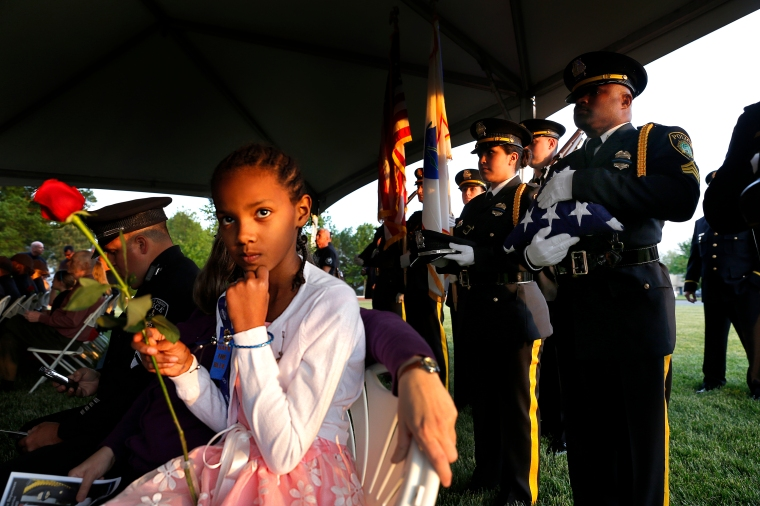 Maya Mercer, left, holds a rose as Newport News police officers wait to place the Flag, Boots and Hat during Thursday's candlelight memorial service to remember the 11 police officers who have died on duty and to honor those who serve today.