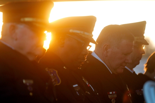 Newport News police officers listen as Retired Sgt. Lenore Whitehead speaks during Thursday's candlelight memorial service to remember the 11 police officers who have died on duty and to honor those who serve today.