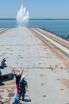Susan Ford Bales raises her arms in triumph as she sees the splash from a deadload she launched from Gerald R. Ford (CVN78) during EMALS testing. Photo by Chris Oxley/Newport News Shipbuilding