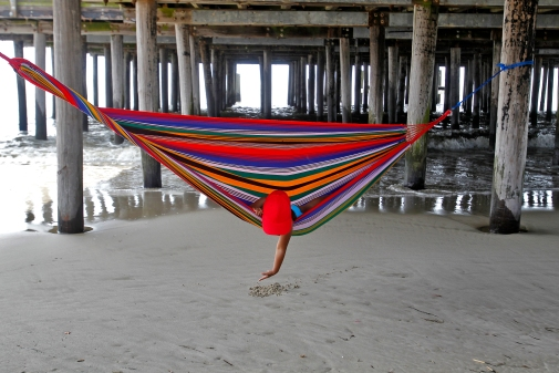 Erica Carcamo, 4, plays in the sand while laying in a hammock as waves wash ashore underneath the pier of Buckroe Beach Friday morning. (Photo by Jonathon Gruenke/Daily Press)
