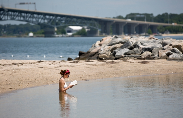 Tori Rhodes sits in the York River to keep cool while reading a book at the Yorktown waterfront on Monday. (Kaitlin McKeown) For More