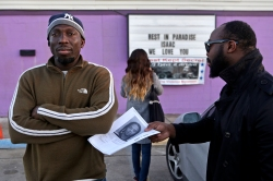 Monsur Dawodu, left, stares off into the distance as Jide Oshin, right, hands back the mugshot of Rashad D'Antrell Ashlock, a 20-year-old who has been arrested and charged in connection with the death of Jide's father, Isaac Oshin, owner of Majik City Gentlemen's Club and Sports Bar. Dozens of people gathered outside the club Friday evening for a vigil to remember Isaac Oshin. Oshin was shot to death Wednesday evening inside the club at 5825 Jefferson Ave. (Photo by Jonathon Gruenke / Daily Press)