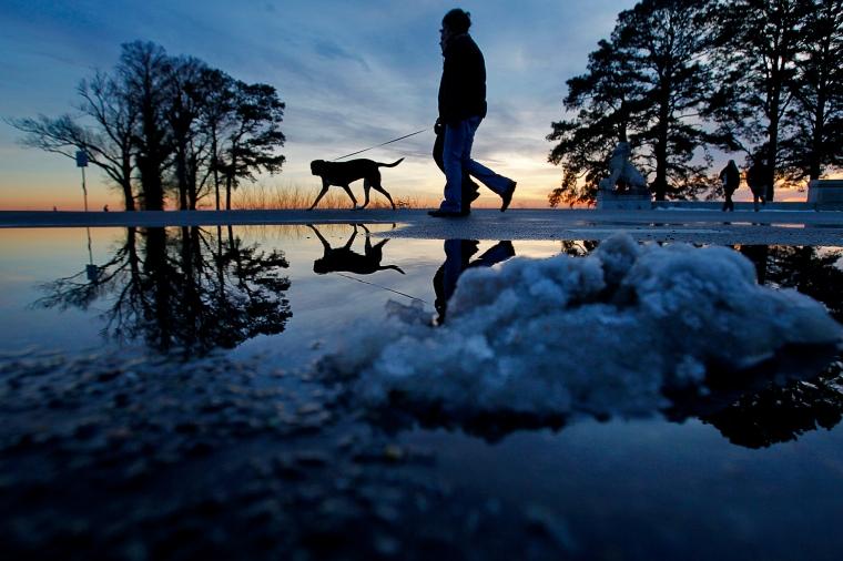 Patrik and Camilla Lasson walk their dog Roxy as snow piles melt while the sun sets Friday evening near Lions Bridge. (Photo by Jonathon Gruenke/Daily Press)