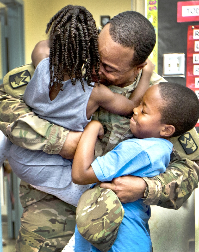 Sgt. Major James Holmes surprises his son inside his class room this morning at Armstrong School for the Arts. U.S. Army Sgt. Major James Holmes had been deployed to Afghanistan for the entire school year. Upon their father's arrival, Adrian 4 yrs. and Aiden 8 yrs. jumped into their fathers arms.