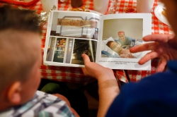 Kyle Summerfield, left, listens as Albert Kurtyka, right, talks and shows a book of being in the hospital while receiving a heart transplant Friday evening at Beach Bully Bbq in Virginia Beach. Albert Kurtyka received the heart of Summerfield's father, William, 34, after he died in a car accident in January 2014.