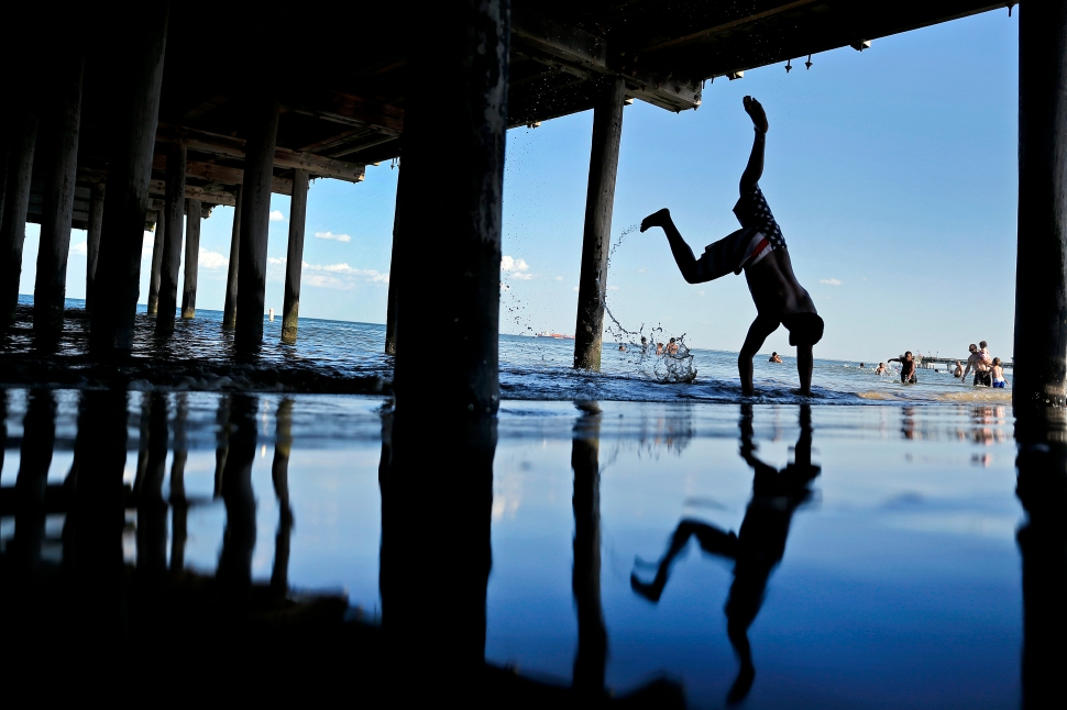 Justin Watson attempts to do a head stand as waves crash into the shore of Buckroe Beach Tuesday afternoon.