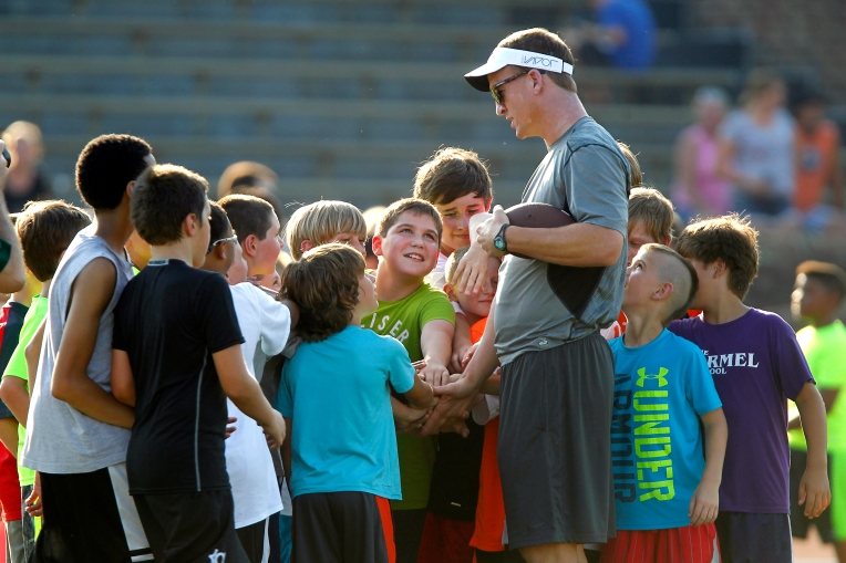 Denver Broncos quarterback Peyton Manning meets with children Sunday evening during William and Mary's Colonial All-Pro Camp.