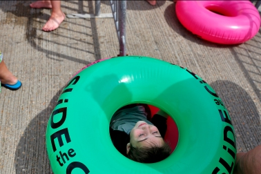 Five-year-old Brennan McCardell rests inside a tube while waiting in line for Saturday's Slide the City event in Hampton.
