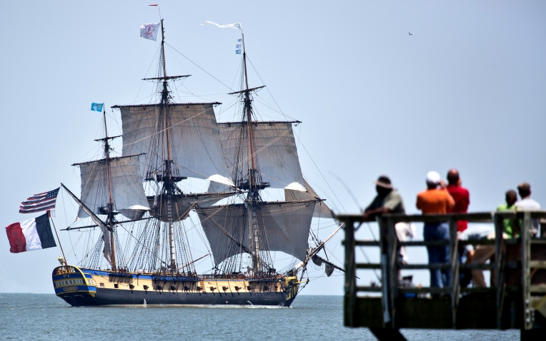 People watch from the fishing pier as the French tall ship Hermione departs from Yorktown on Monday afternoon. (Joe Fudge/Daily Press)