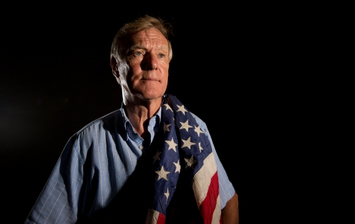 Retired Senior Chief Petty Officer Tim Johnson holds an American flag retrieved from a swift boat after a recoiless rifle attack in the Song Tra Bong River in November 1968 during his service in the Vietnam War.