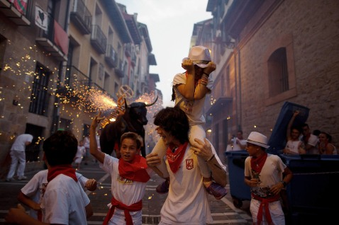 People and children are chased by the 'Toro de Fuego' (flaming bull) as it runs throught the streets during the opening day of the San Fermin Running of the Bulls fiesta on July 6, 2015 in Pamplona, Spain. (Photo by Pablo Blazquez Dominguez/Getty Images)