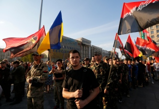 Members of the Right Sector group march down the street during a rally in the center Kiev, Ukraine, Tuesday, July 21, 2015. The radical Right Sector group was one of the most militant factions in the massive protests in Ukraine's capital that prompted pro-Russia President Viktor Yanukovych to flee the country in February 2014. Since war broke out in eastern Ukraine between government forces and pro-Russia separatists several months later, the Right Sector has fought on the government side. (AP Photo/Sergei Chuzavkov)