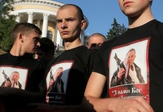 Members of the Right Sector group march down the street wearing tshirts depicting Sashko Bily, leader of the Right Sector group who was killed during a police raid last year, during a rally in the center Kiev, Ukraine, Tuesday, July 21, 2015. The radical Right Sector group was one of the most militant factions in the massive protests in Ukraine's capital that prompted pro-Russia President Viktor Yanukovych to flee the country in February 2014. Since war broke out in eastern Ukraine between government forces and pro-Russia separatists several months later, the Right Sector has fought on the government side. (AP Photo/Efrem Lukatsky)