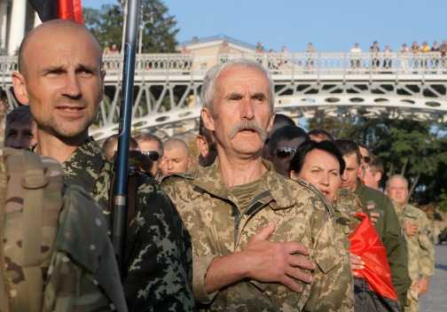 Members of the right sector sing the national anthem during a rally in center Kiev, Ukraine, Tuesday, July 21, 2015. The radical Right Sector group was one of the most militant factions in the massive protests in Ukraine's capital that prompted pro-Russia President Viktor Yanukovych to flee the country in February 2014. Since war broke out in eastern Ukraine between government forces and pro-Russia separatists several months later, the Right Sector has fought on the government side. (AP Photo/Efrem Lukatsky)