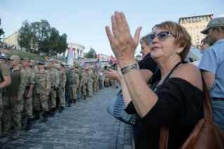 People applause to members of the Right Sector group march down the street during a rally in the center Kiev, Ukraine, Tuesday, July 21, 2015. The radical Right Sector group was one of the most militant factions in the massive protests in Ukraine's capital that prompted pro-Russia President Viktor Yanukovych to flee the country in February 2014. Since war broke out in eastern Ukraine between government forces and pro-Russia separatists several months later, the Right Sector has fought on the government side. (AP Photo/Efrem Lukatsky)