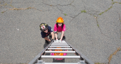 Newport News fire Capt. Naomi Nichols, left, helps a young girl set a ladder against a training tower during an exercise on Monday at Camp Fury, a camp for girls hosted by the Hampton Division of Fire and Rescue. (Kaitlin McKeown)