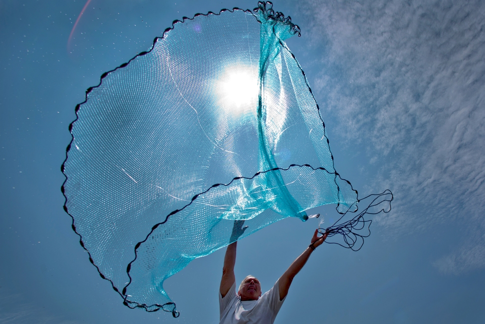 Retired Army Lt. Col. Clem Danish of Newport News casts his bait fish net out over the water at the end of Messick Rd. in Poquoson. Danish was in search of baitfish but came up empty on his attempt.  (Joe Fudge) For More