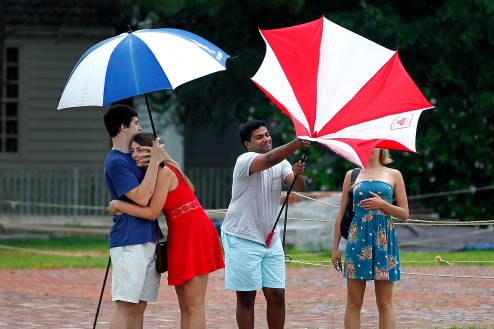 Patrick McMahon, left, holds Maggie McDevitt as John Dunigan attempts to open an umbrella with Molly Burke in along Duke of Gloucester Street in Colonial Williamsburg Saturday afternoon. (Jonathon Gruenke)