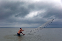 Alexander Chebec casts a net into the James River along the Colonial Parkway as storm clouds look in the distance Saturday afternoon. (Jonathon Gruenke)