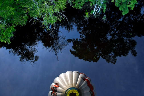 Pilot Reed Basley's hot air balloon is reflected in a body of water near Lanexa Monday evening. (Photo by Jonathon Gruenke/Daily Press)