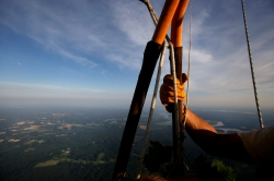 Pilot Reed Basley holds onto the basket while floating through the skies in his hot air balloon Monday evening. (Photo by Jonathon Gruenke/Daily Press)
