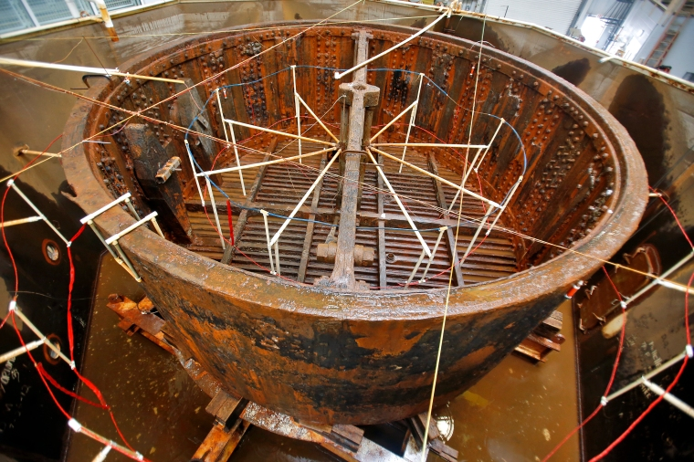 The Monitor turret treatment tank on Monday, Aug. 27, 2015 was exposed from beneath an alkaline solution for the first time in three years. It takes 4 1/2 hours to drain 90,000 gallons from the treatment tank. To the left is conservator assistant Tina Gutshall. (Jonathon Gruenke)