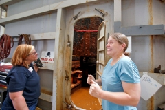 Conservator Kate Sullivan, right, reacts after opening the door to the Monitor turret treatment tank on Monday, Aug. 27, 2015. The turret was exposed from beneath an alkaline solution for the first time in three years. It takes 4 1/2 hours to drain 90,000 gallons from the treatment tank. To the left is conservator assistant Tina Gutshall. (Jonathon Gruenke)